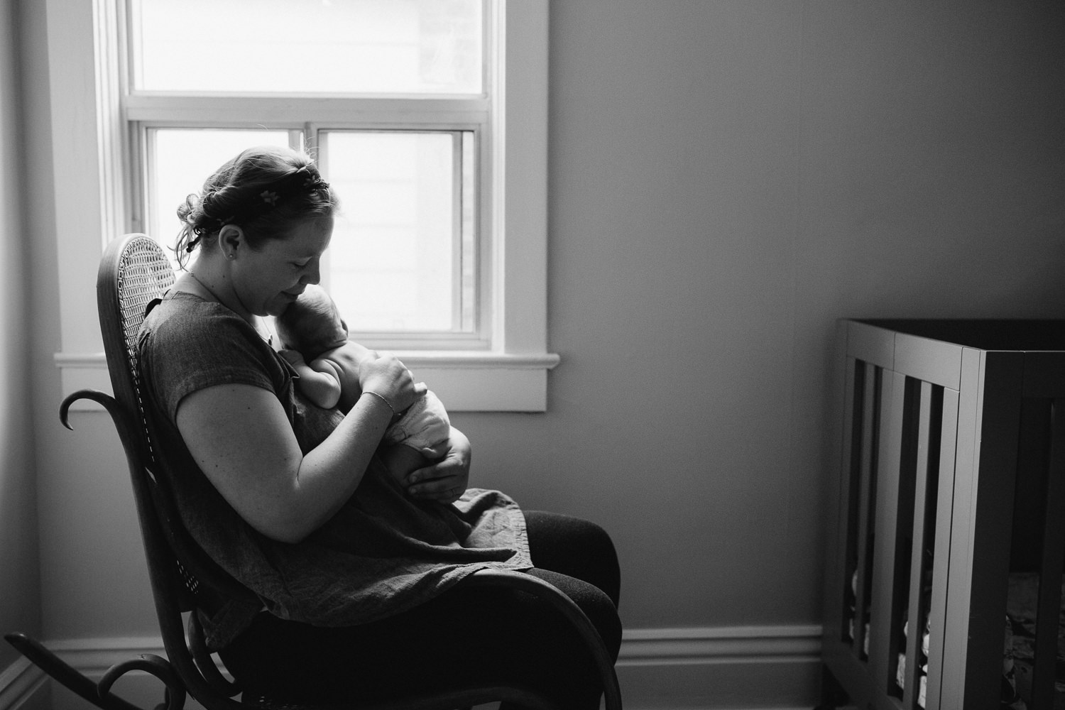 mom sitting in nursery rocker cuddling 10 day old baby boy on chest - Newmarket Lifestyle Family Photos