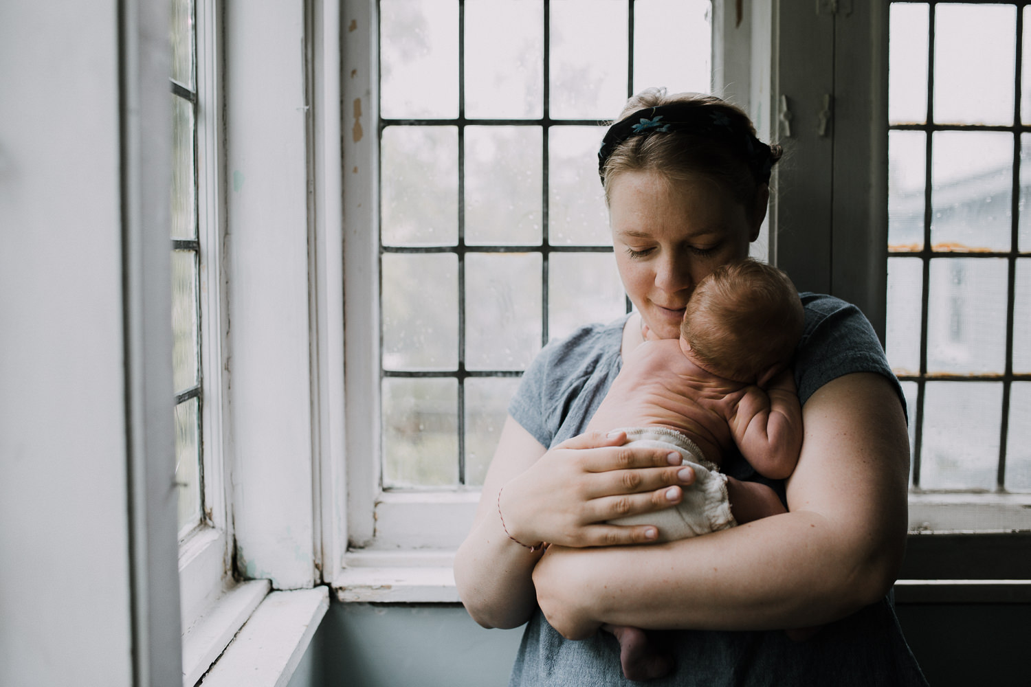 mom standing and cuddling 10 day old baby boy on chest - Barrie Lifestyle Family Photos