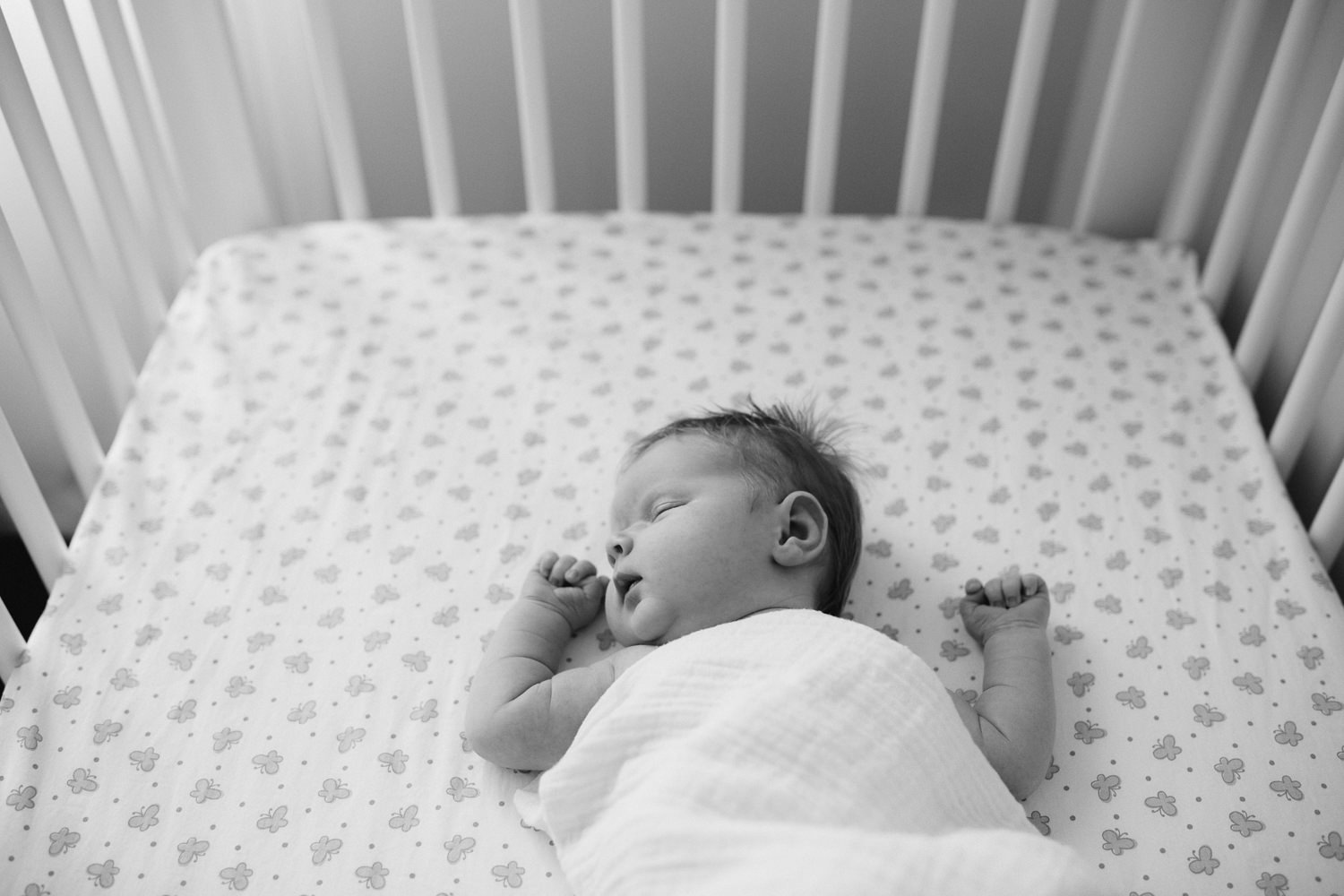 2 week old swaddled baby girl with red hair asleep in nursery crib - Markham In-Home Photos