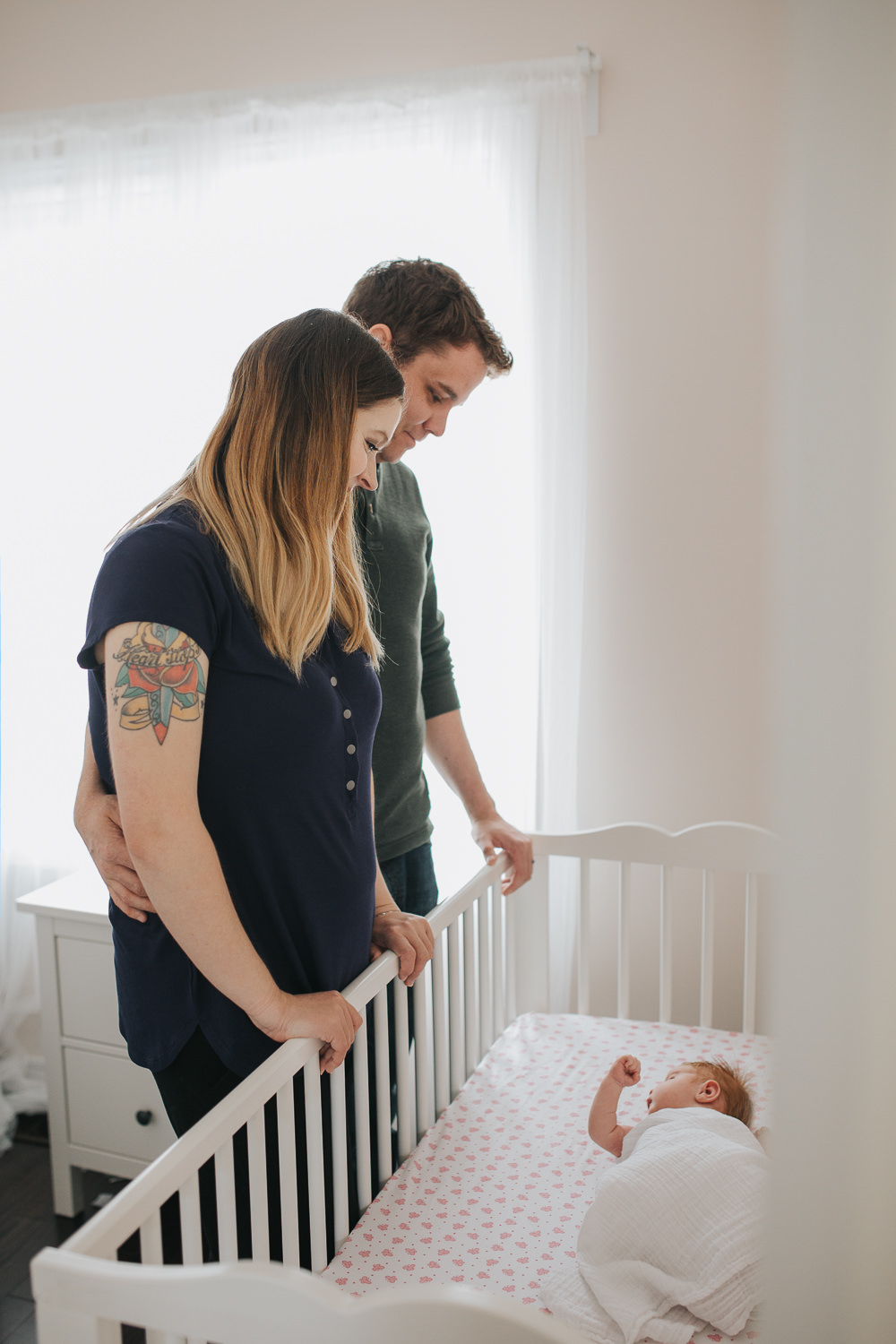 parents stand in nursery  looking at 2 week old swaddled baby girl with red hair asleep  crib - Newmarket Lifestyle Photos