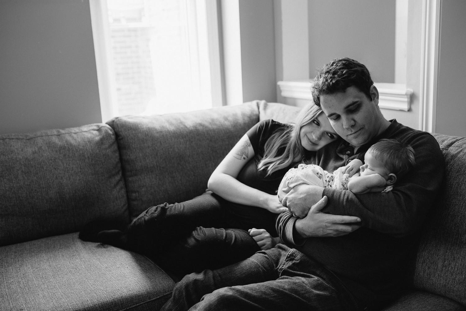 family of 3, new parents sitting on couch holding and looking at 2 week old baby girl - Barrie In-Home Photography