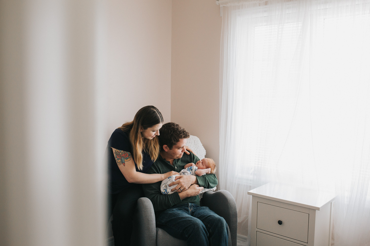 new parents sitting in nursery chair holding 2 week old baby girl with red hair - Stouffville In-Home Photos