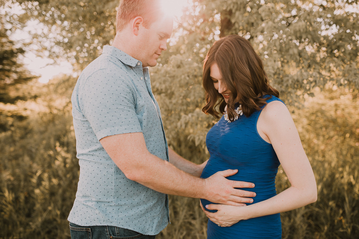 pregnant brunette mom-to-be standing with husband as he holds her belly at sunset - Newmarket Lifestyle Photography