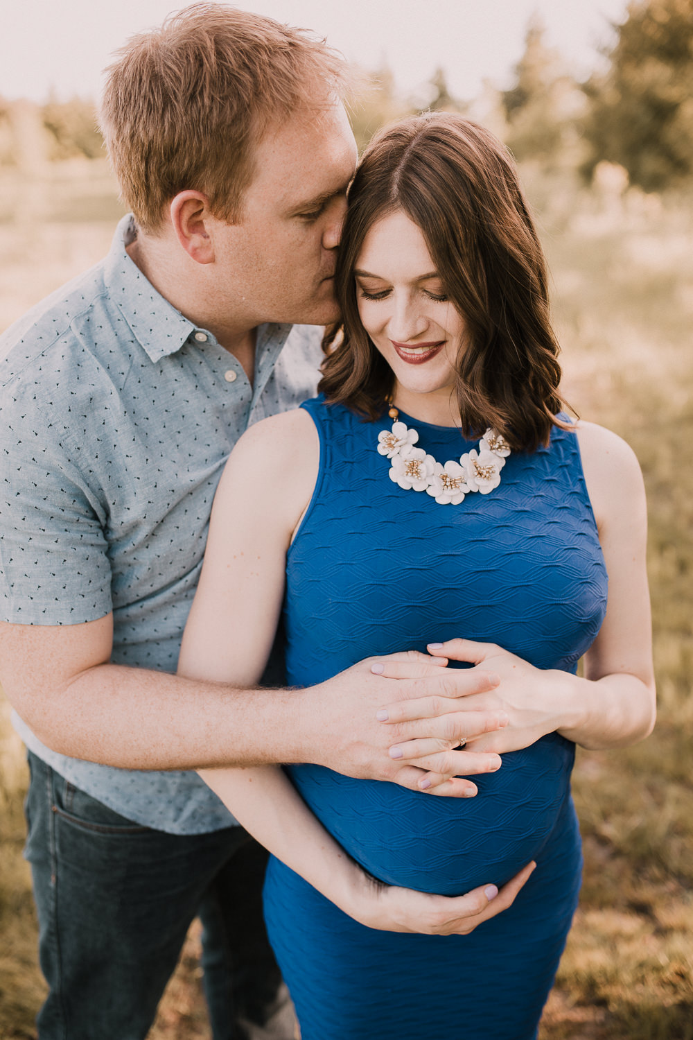 husband embraces pregnant wife in blue dress and kisses her on cheek at sunset - Barrie Lifestyle Photos