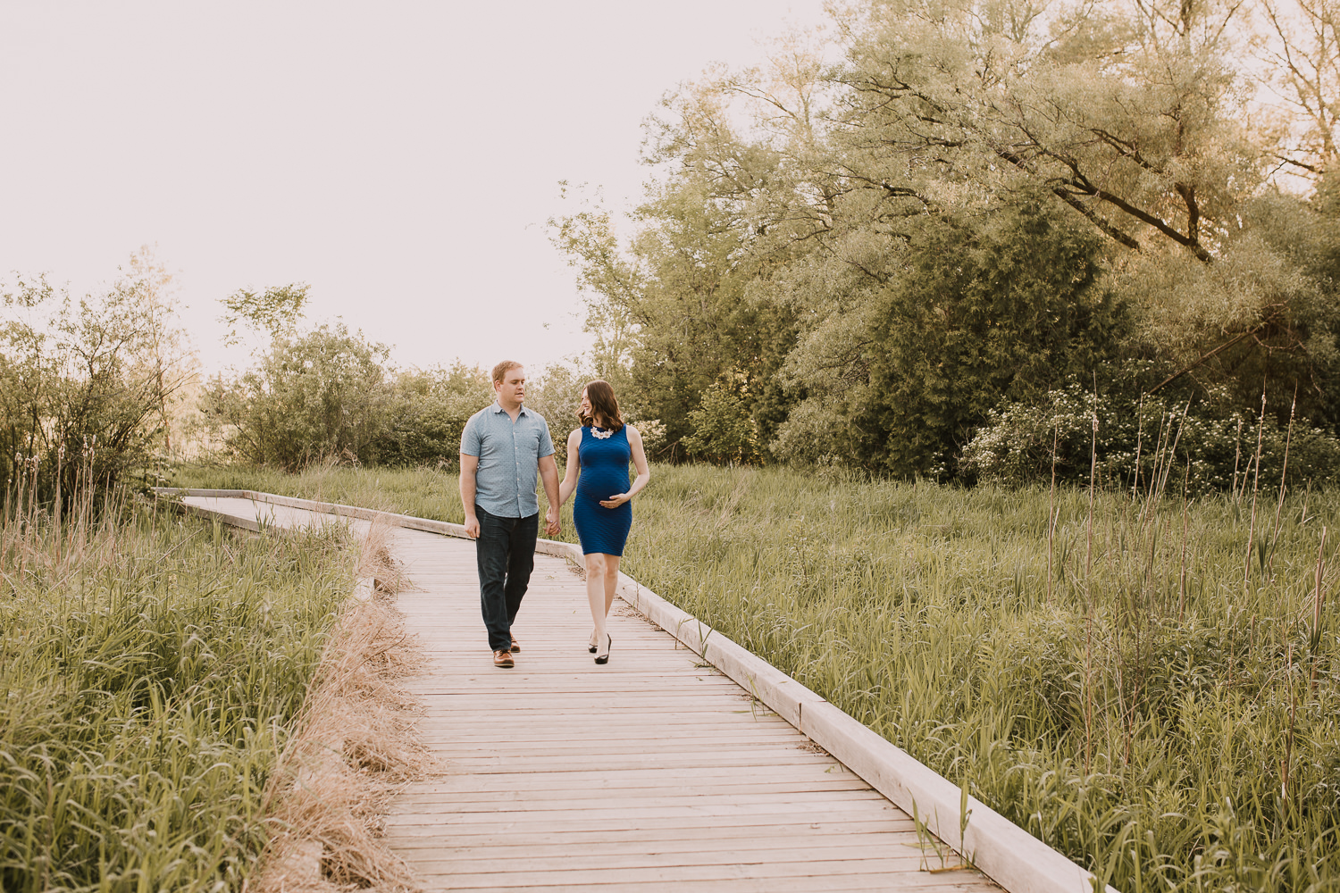 pregnant brunette mom-to-be holds husband's hand as they walk along bridge - Markham Outdoor Photography