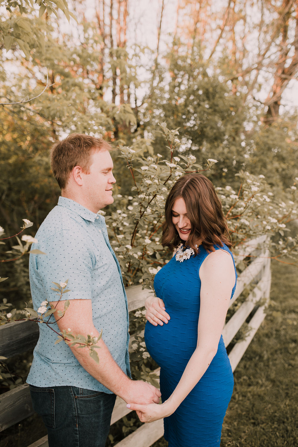 pregnant brunette mom-to-be in blue dress holding husband's hand as he smiles at her - Markham Outdoor Photos