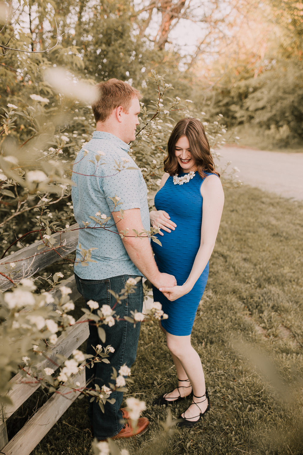 pregnant brunette mom-to-be in blue dress smiles, holding husband's hand - Barrie Outdoor Photos