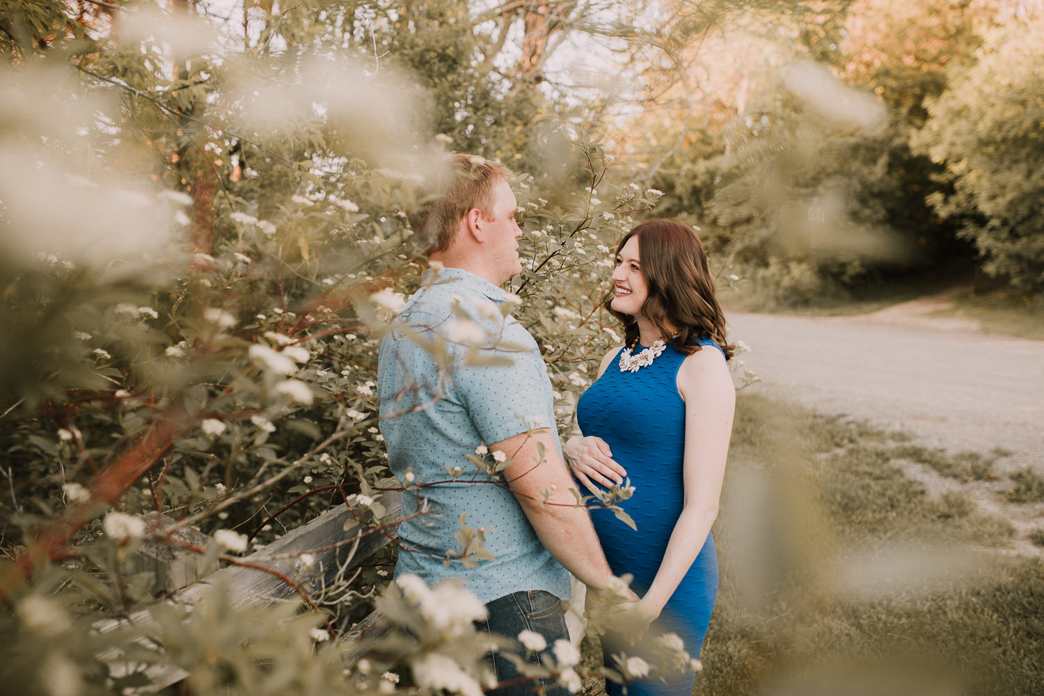 pregnant brunette mom-to-be in blue dress holding husband's hand and smiles at him - Newmarket Lifestyle Photography