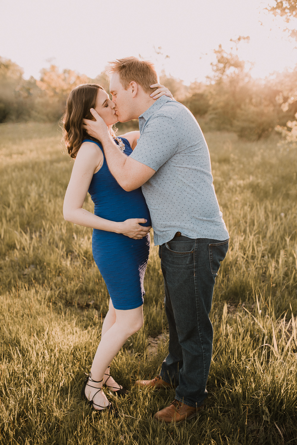 father-to-be kissing pregnant brunette wife in golden field at sunset - Markham Lifestyle Photos