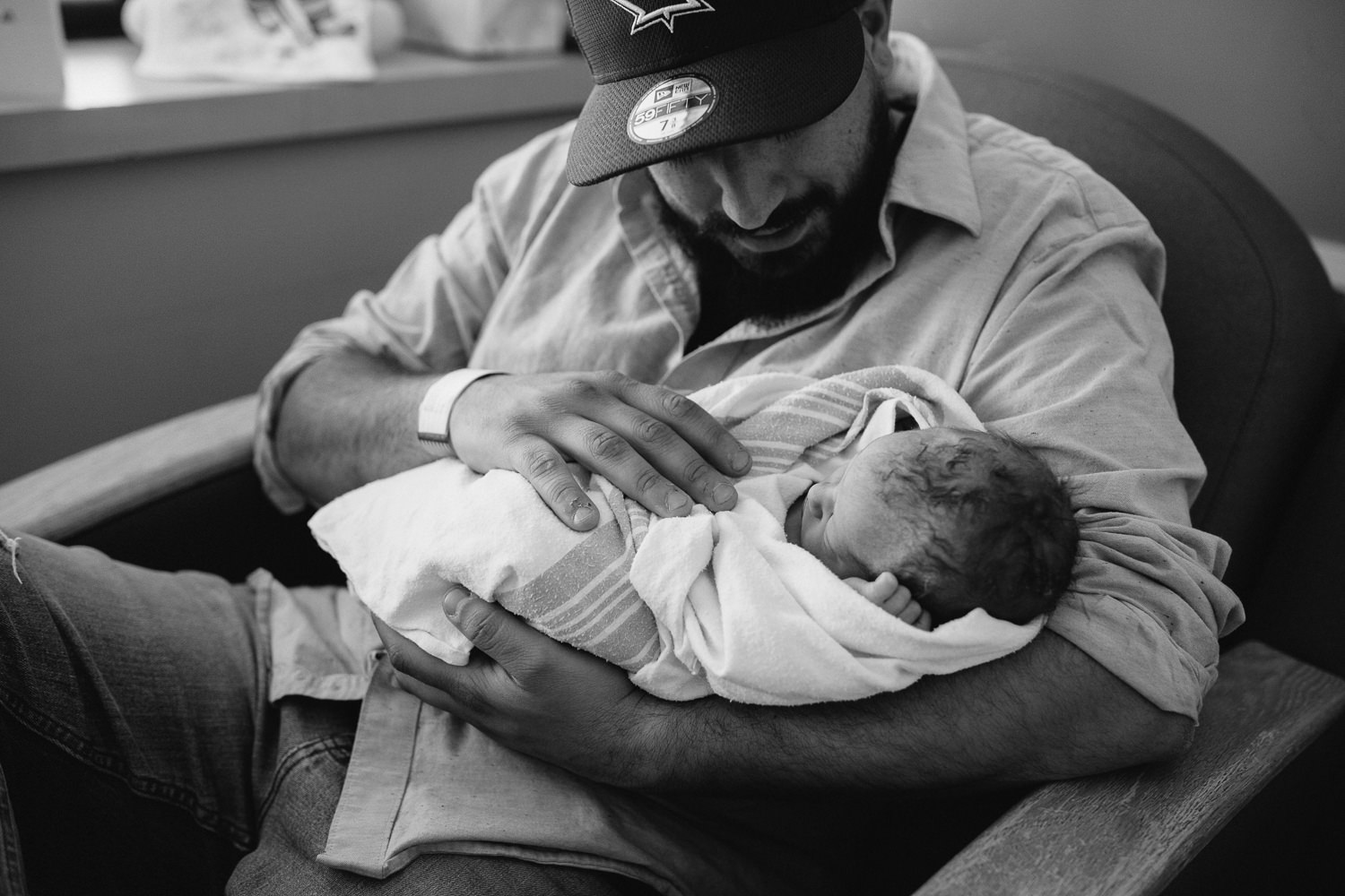 new dad sitting in hospital chair holding swaddled, sleeping 10 hour old baby boy - Newmarket In-Hospital Photography