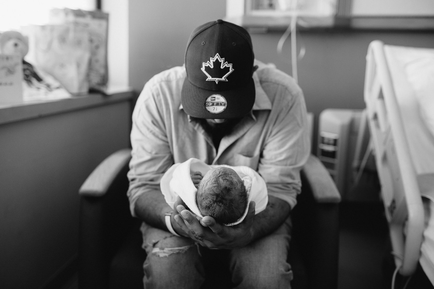new dad sitting in hospital chair holding swaddled, sleeping 10 hour old baby boy - Markham Fresh 48 Photography
