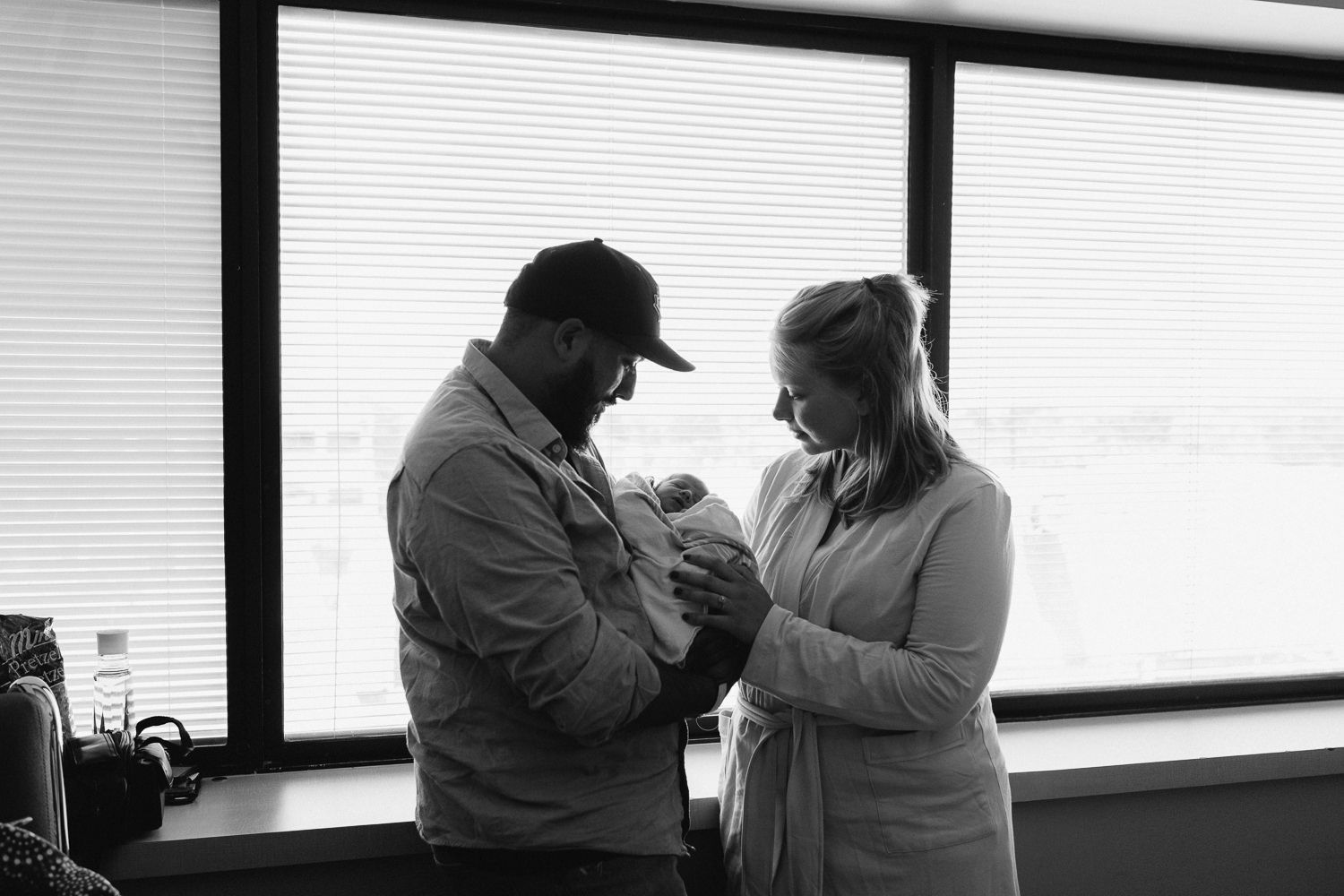 first time parents standing in hospital room holding and looking at 10 hour old baby boy - Barrie Fresh 48 Photos