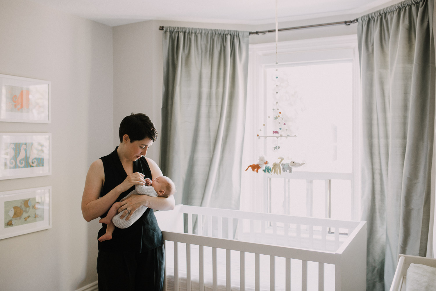 first time mom holding baby boy standing in front of nursery crib - Barrie In-Home Photos