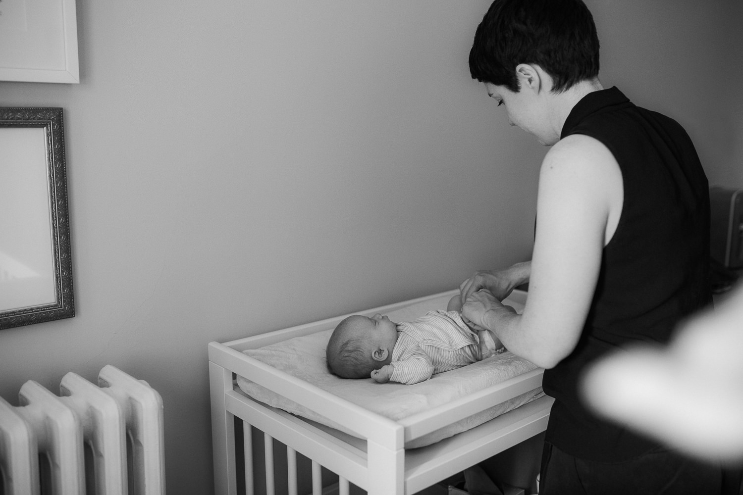 new mother changing 2 week old baby boy's diaper in nursery - Barrie Lifestyle Photography