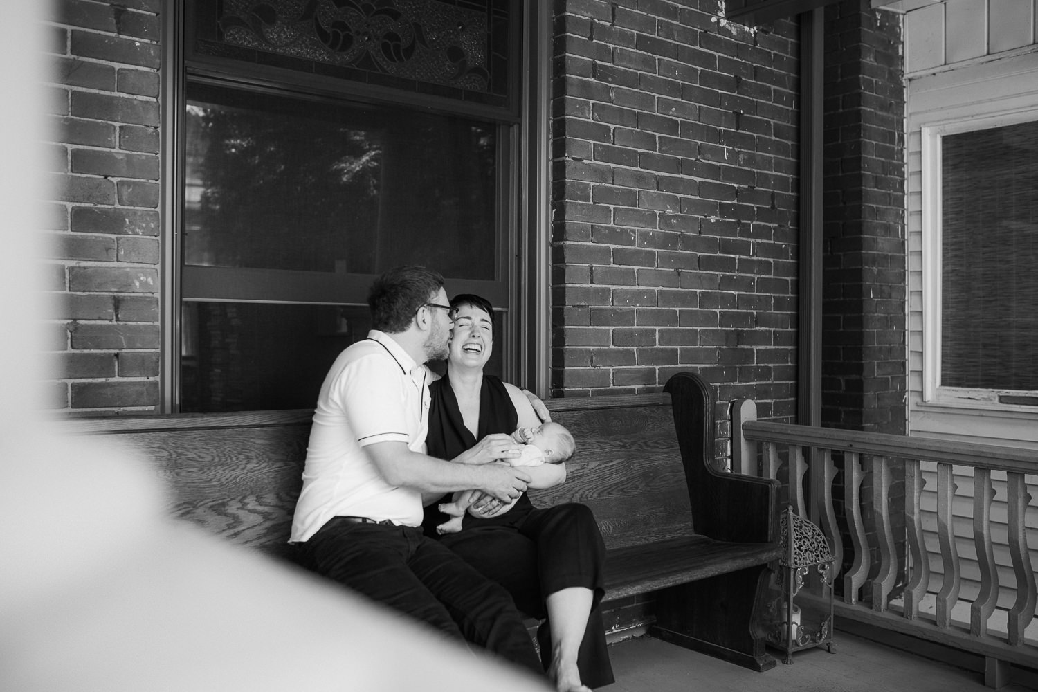 new parents sitting on front porch holding sleeping 2 week old baby boy, dad kissing mom's cheek - Barrie In-Home Photos