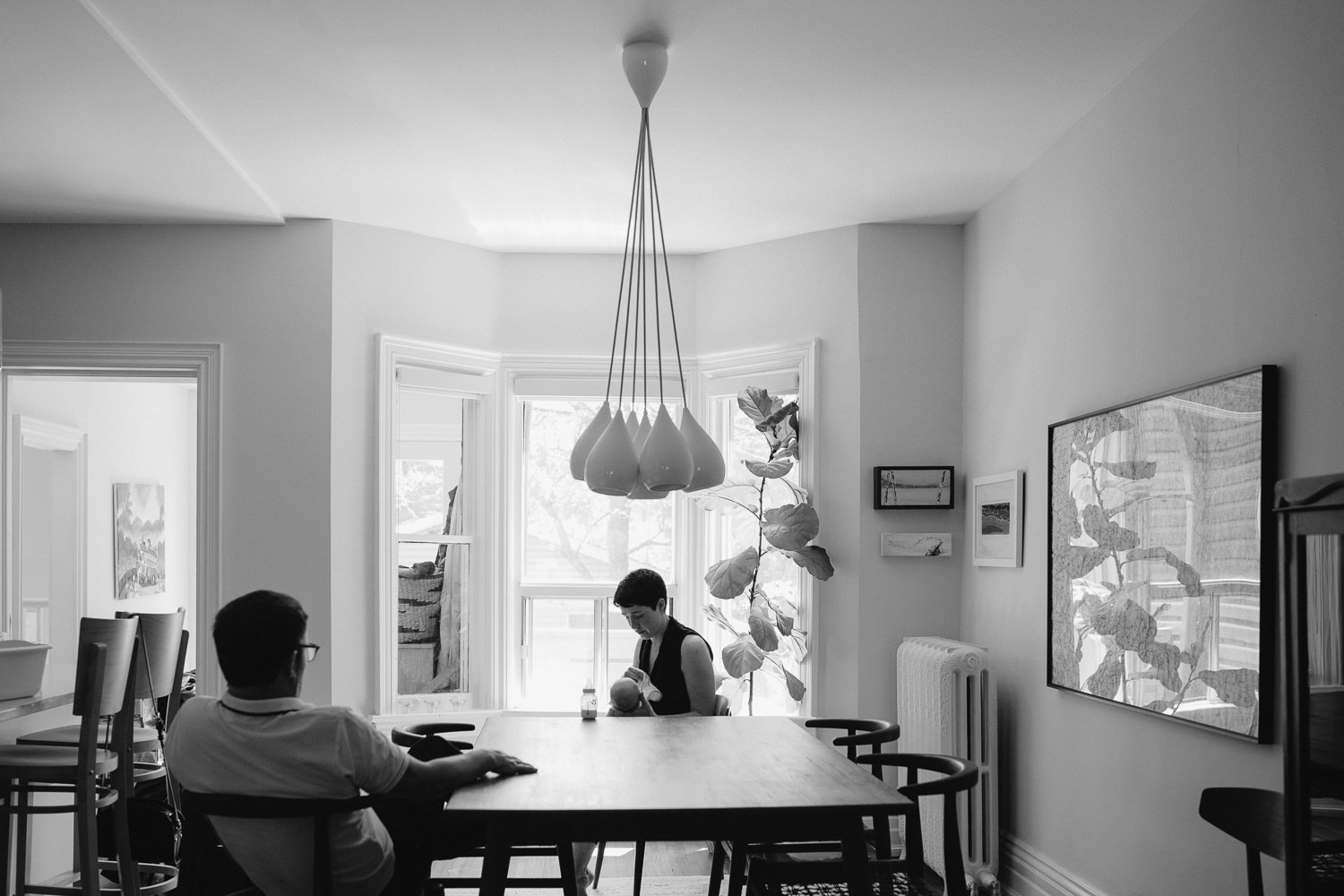 mom and dad sitting in dining room chairs, mother bottle feeding 2 week old baby boy - Barrie Lifestyle Photography