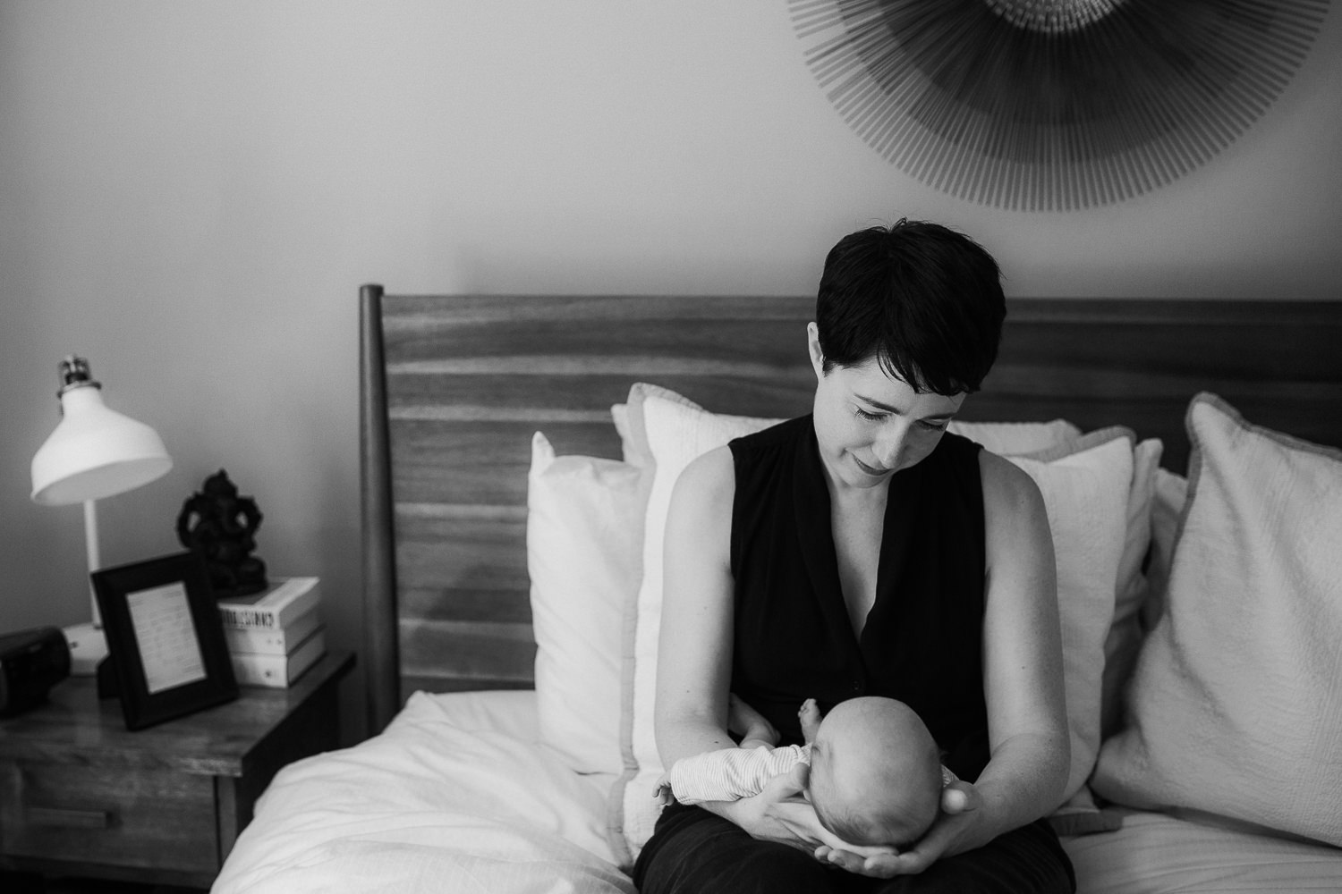 new mom sitting on master bed, 2 week old baby boy sleeping in her arms - Newmarket Lifestyle Photos