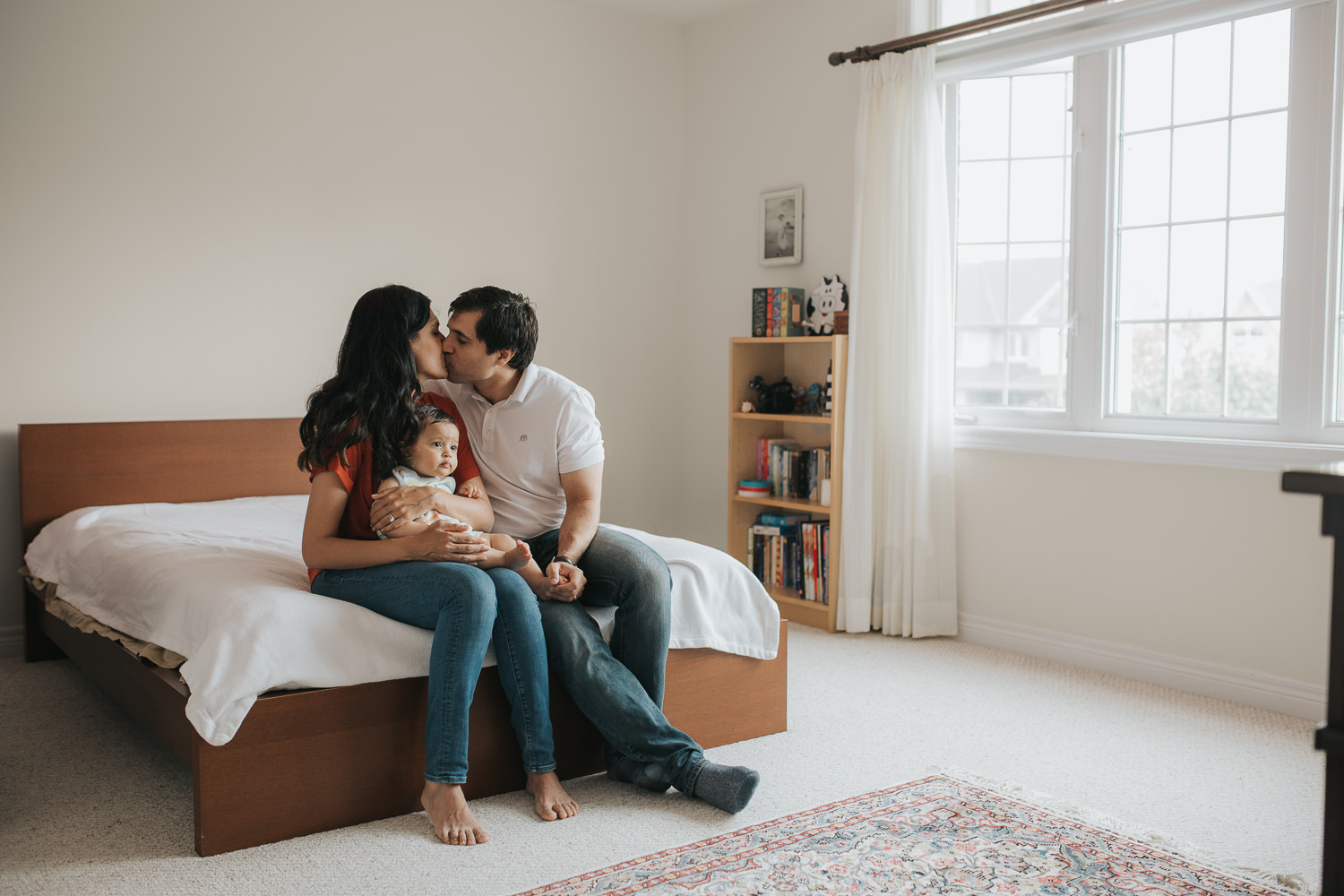 family of 3 sitting on bed, mom holding 8 month old baby boy in lap, husband and wife kissing - Stouffville Lifestyle Photos