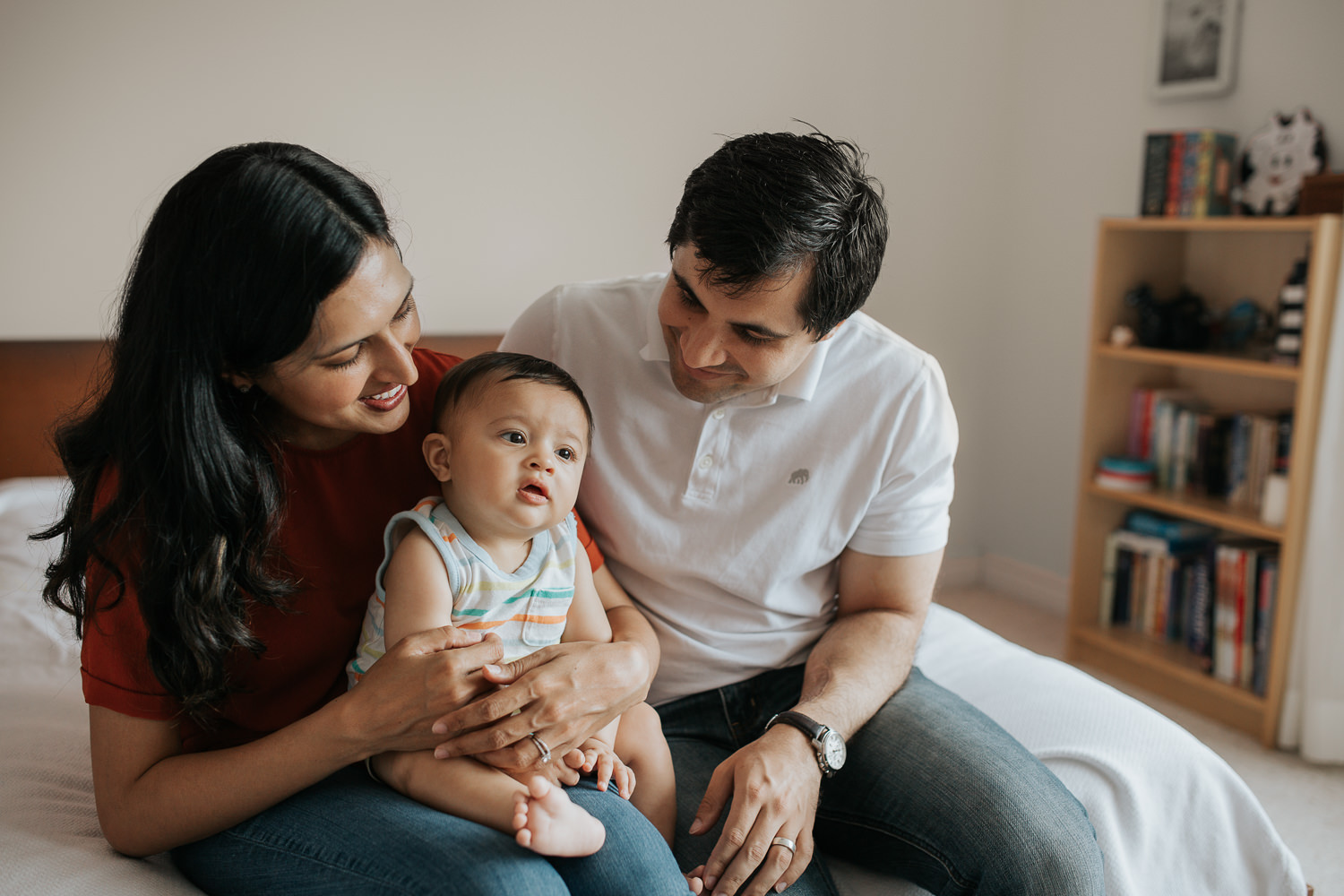 family of 3 sitting on bed, mom holding 8 month old baby boy in lap - Barrie Lifestyle Photos