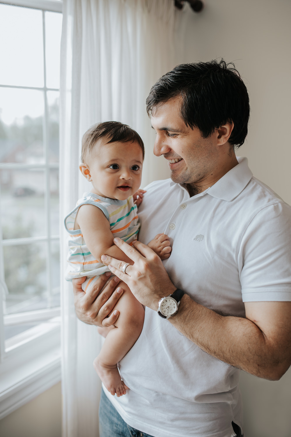 dad standing, holding and smiling at 8 month old baby boy who is smiling up at the ceiling - Newmarket In-Home Photography