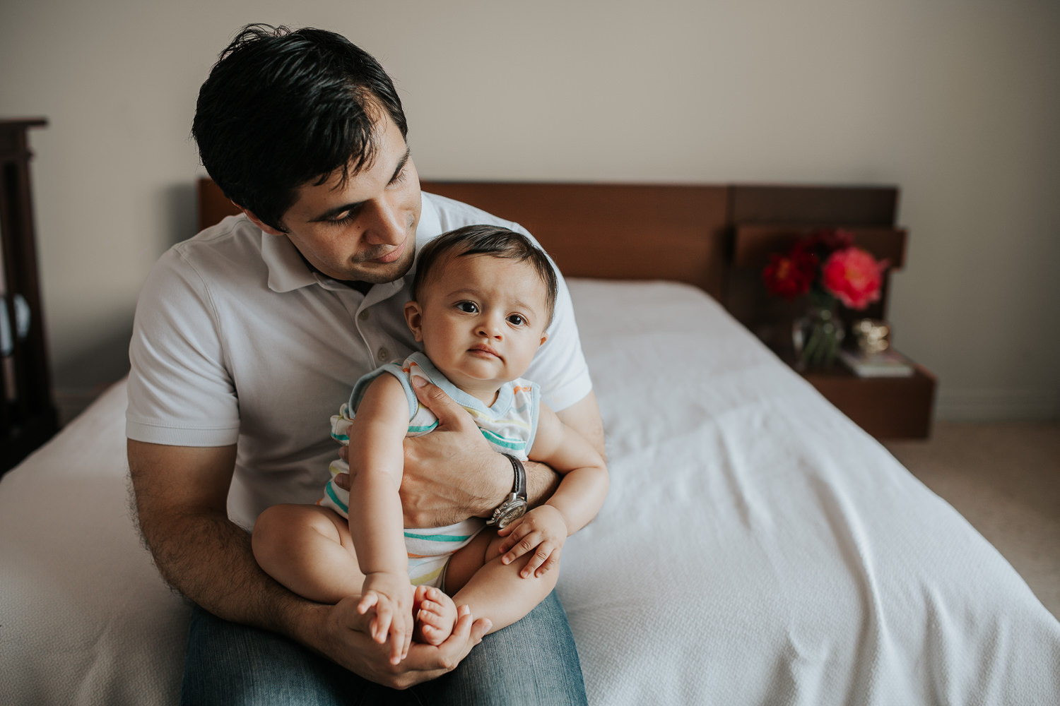 father sitting on bed with 8 month old baby boy in his lap, smiling at son who looks on - Stouffville In-Home Photography