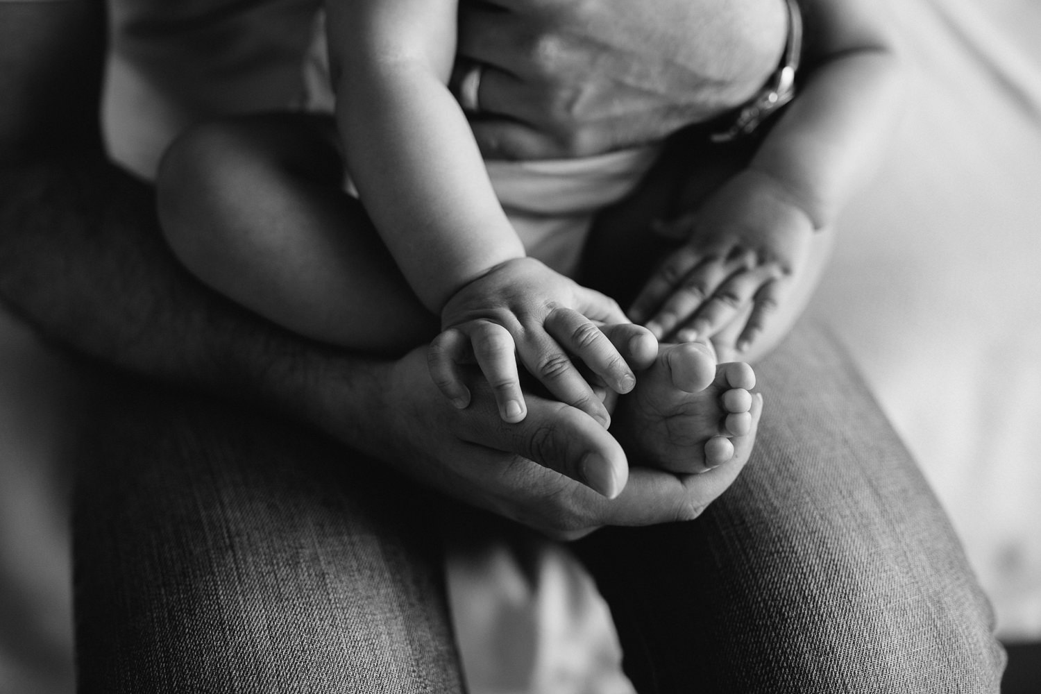 8 month old baby boy sitting in father's lap, close up of hands and feet - Barrie In-Home Photography