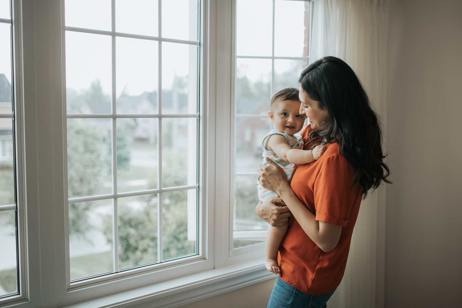 mom standing at window with 8 month old baby boy who is smiling at camera -  Newmarket Lifestyle Photos