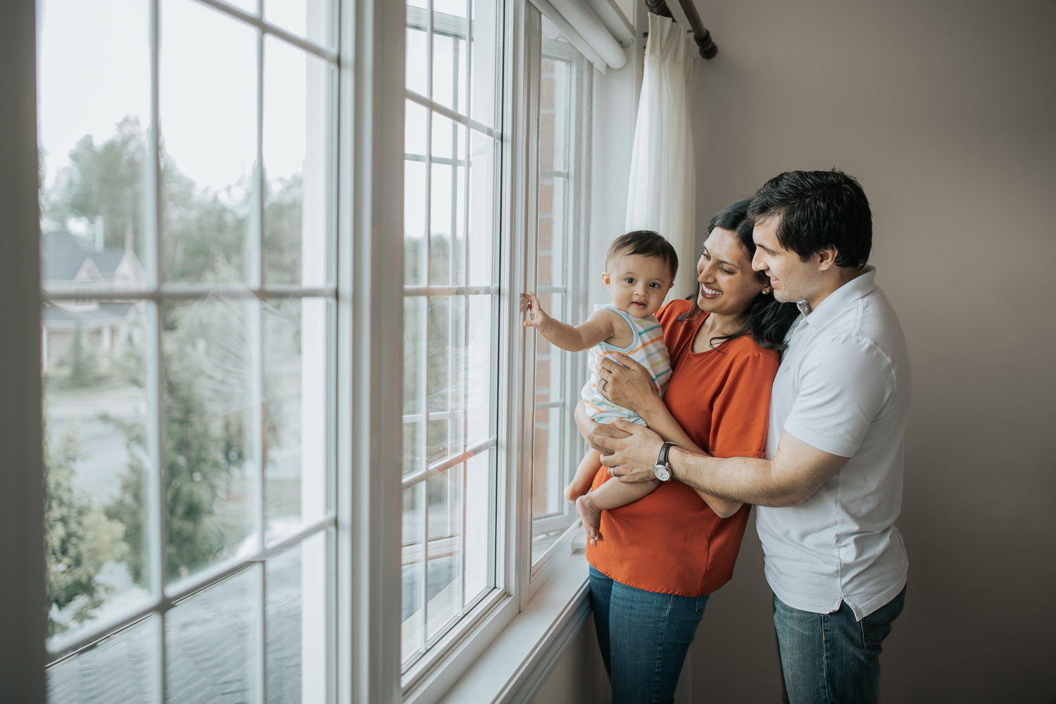 family of 3 standing at window, mom holding 8 month old baby boy - Markham Lifestyle Photos