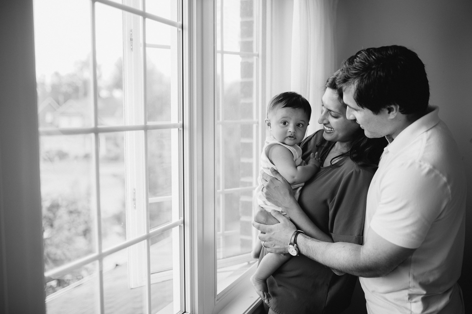 family of 3 standing at window, mom holding 8 month old baby boy - Barrie Lifestyle Photos