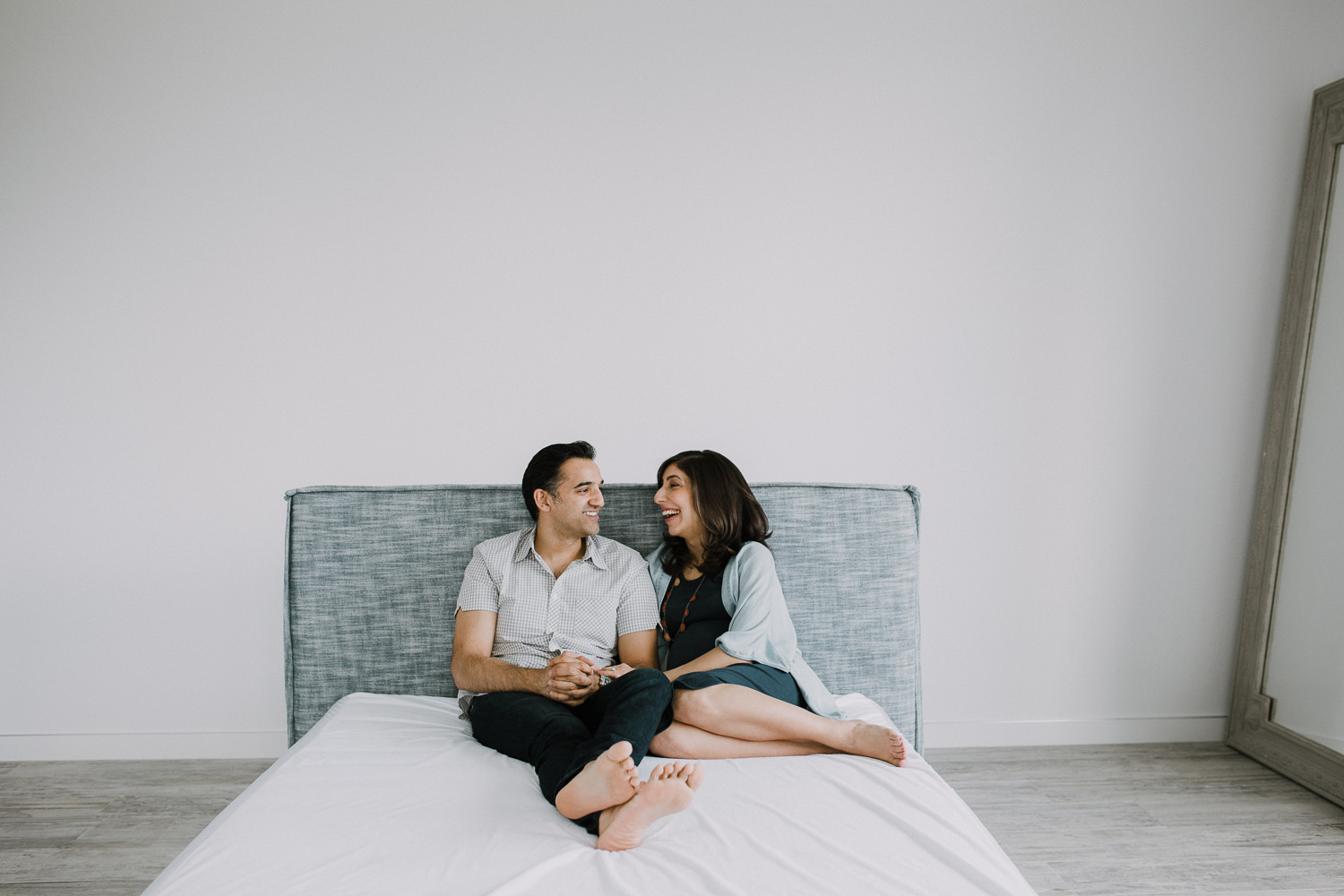 expectant couple sitting on bed laughing and smiling - Newmarket In-Home Photography