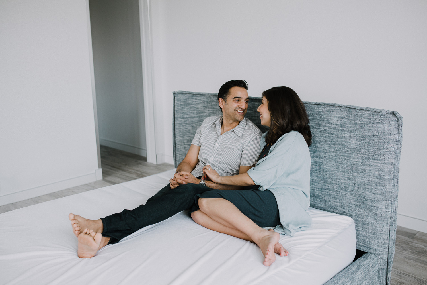 expectant couple sitting on bed, husband smiling at pregnant wife - Stouffville In-Home Photography