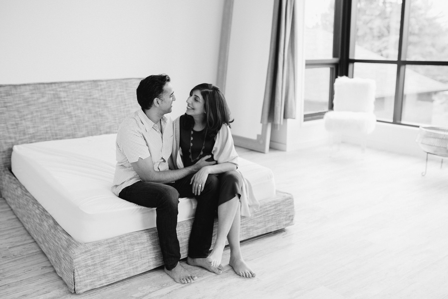 expectant parents sitting at end of bed, pregnant wife smiling at husband - Newmarket In-Home Photos