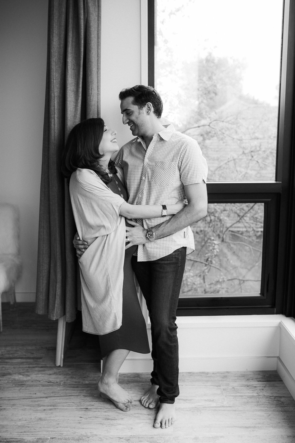 husband and pregnant wife embracing and smiling at one another, standing next to window - Barrie In-Home Photos