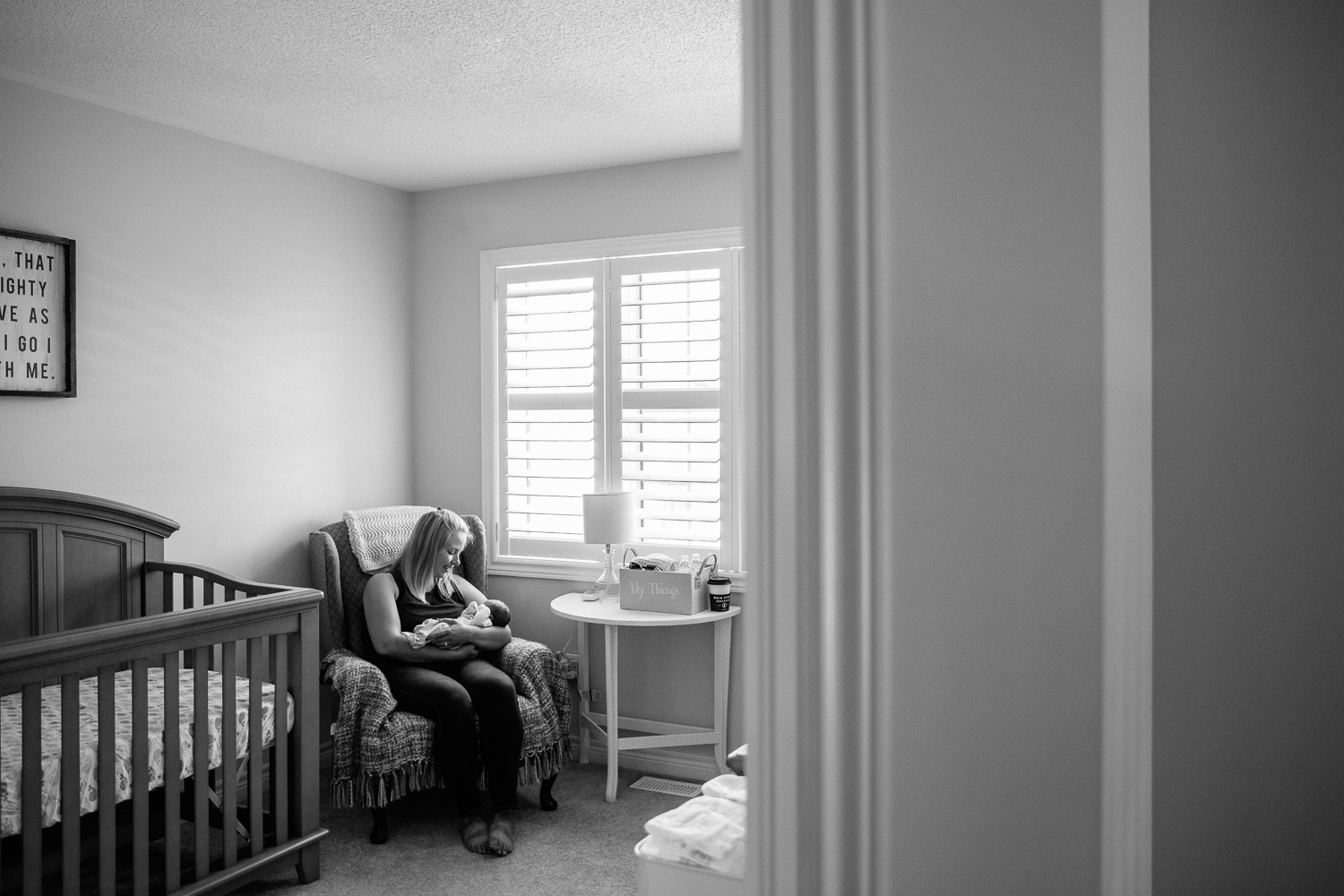 new mom sitting in nursery chair holding 2 week old baby boy - Newmarket Lifestyle Photography