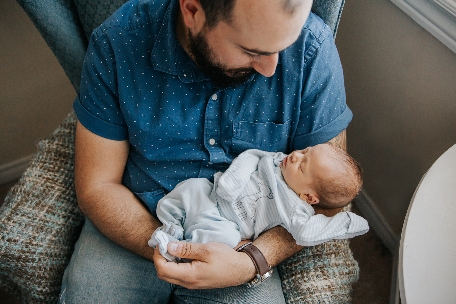 new mom sitting in nursery chair holding 2 week old baby boy in blue sleeper - Stouffville In-Home Photography