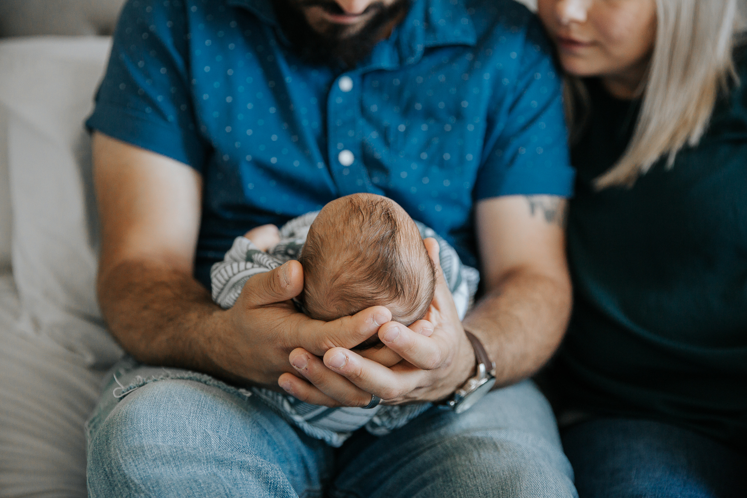 new father sitting on bed, holding 2 week old baby boy's head in his hands - Barrie In-Home Photos