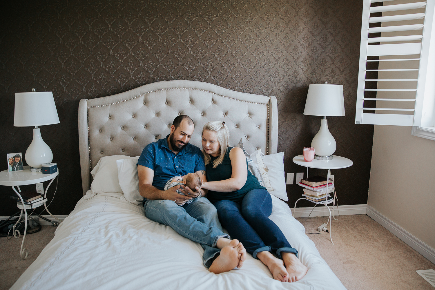 new family of 3 sitting on bed, parents smiling at 2 week old baby boy in dad's arms - Barrie Lifestyle Photos