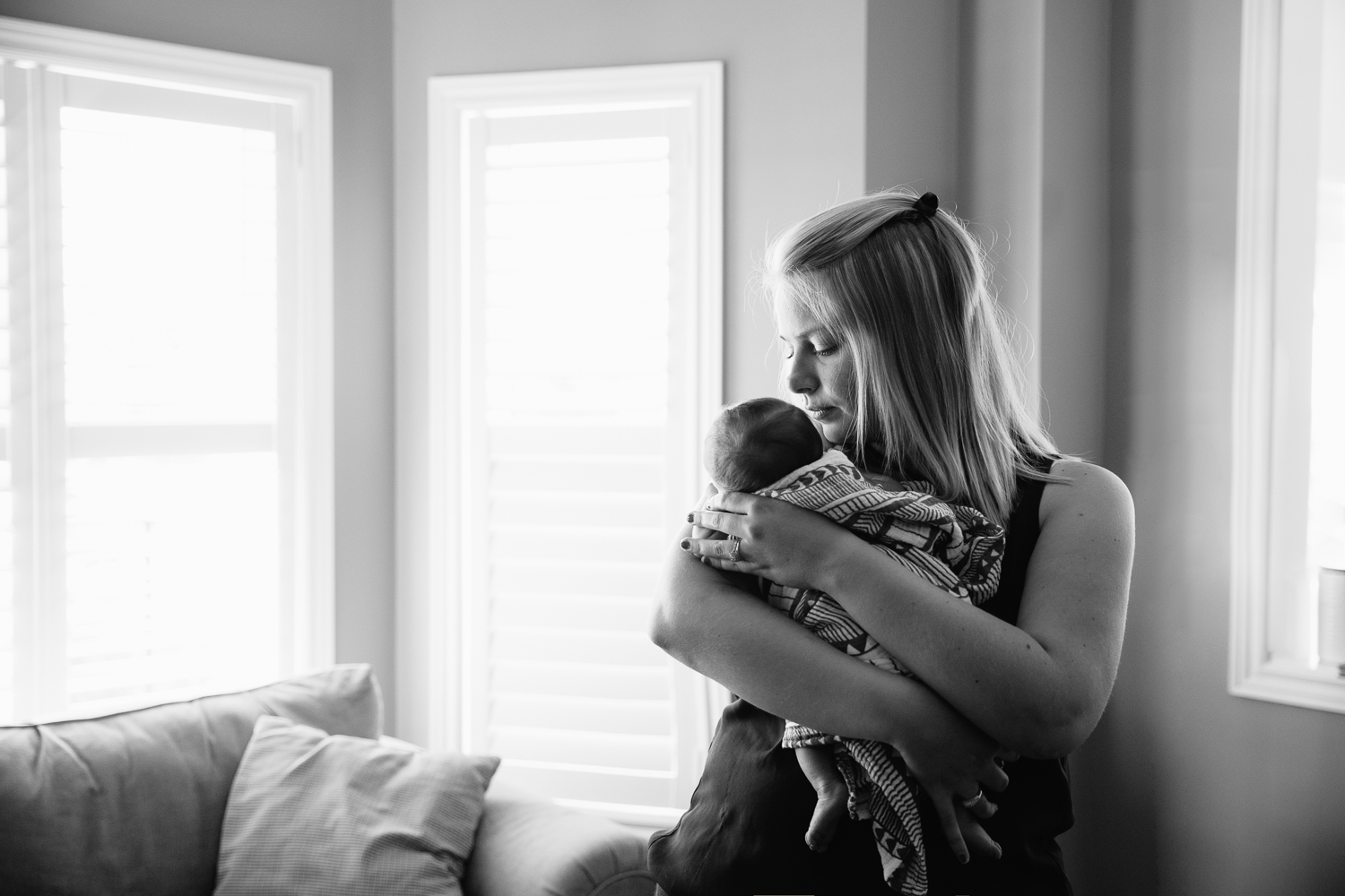 new mom standing in front of window rocking 2 week old baby boy to sleep - Stouffville Lifestyle Photography