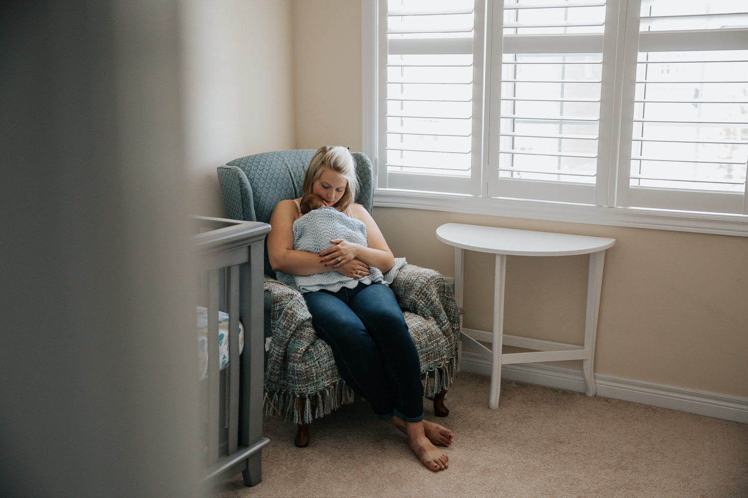 new mom sitting in rocking chair with 2 week old baby boy sleeping snuggled to her chest - Stouffville In-Home Photography