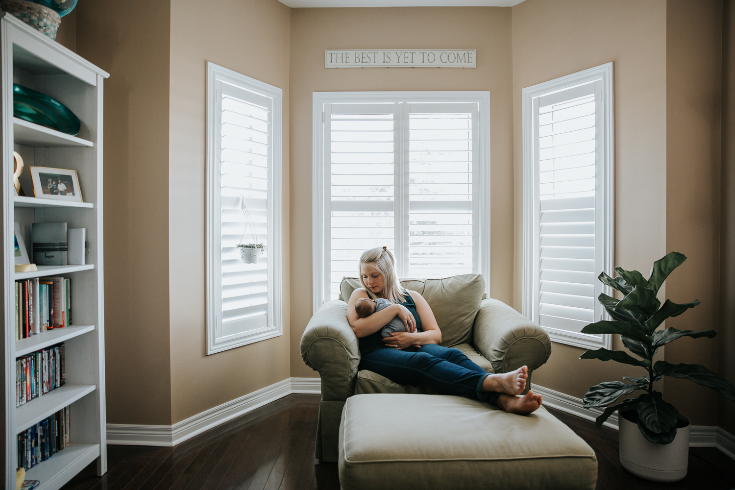 new mom with blonde hair sitting in large chair holding 2 week old baby boy - Markham Lifestyle Photography