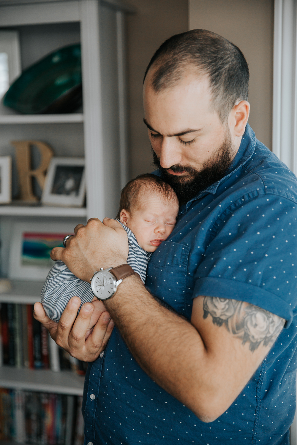 new father standing, snuggling sleeping 2 week old baby boy to his chest -Newmarket In-Home Photos