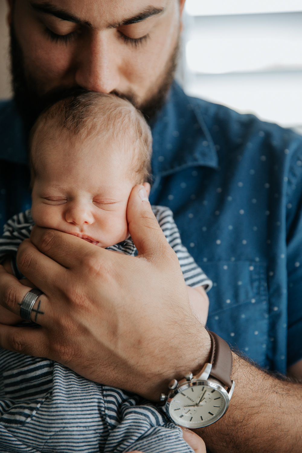 dad holding 2 week old baby boy against his chest, kissing top of his head -Stouffville In-Home Photos