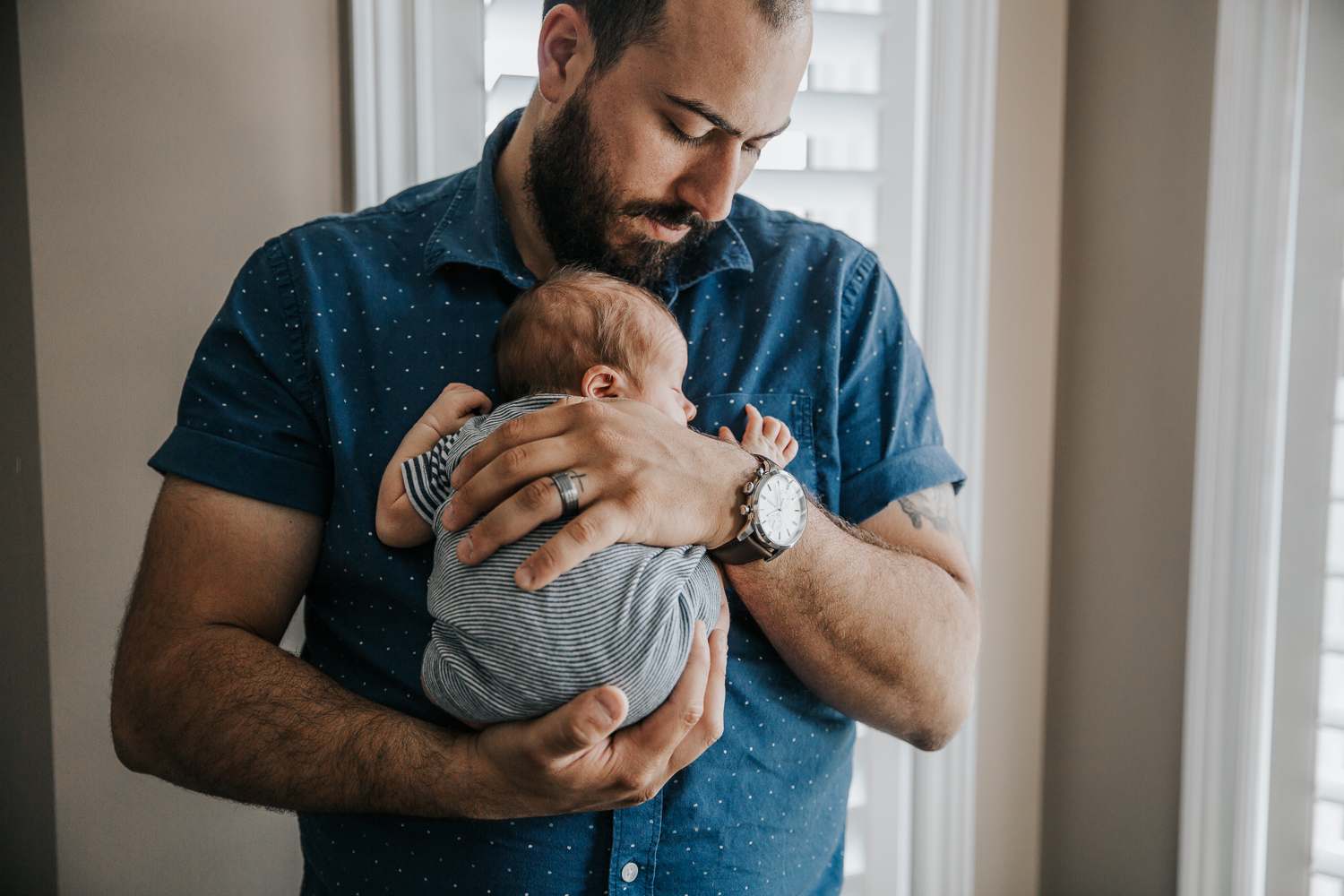 new father standing, snuggling sleeping 2 week old baby boy to his chest - Barrie In-Home Photos