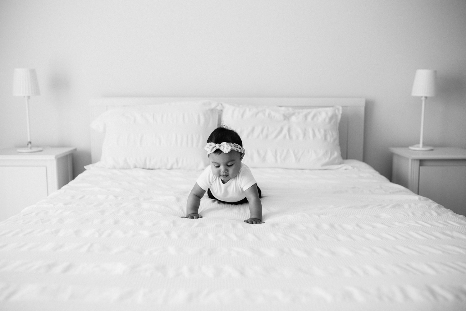6 month old baby girl with floral headband on crawling on white bed - Stouffville Lifestyle Photography