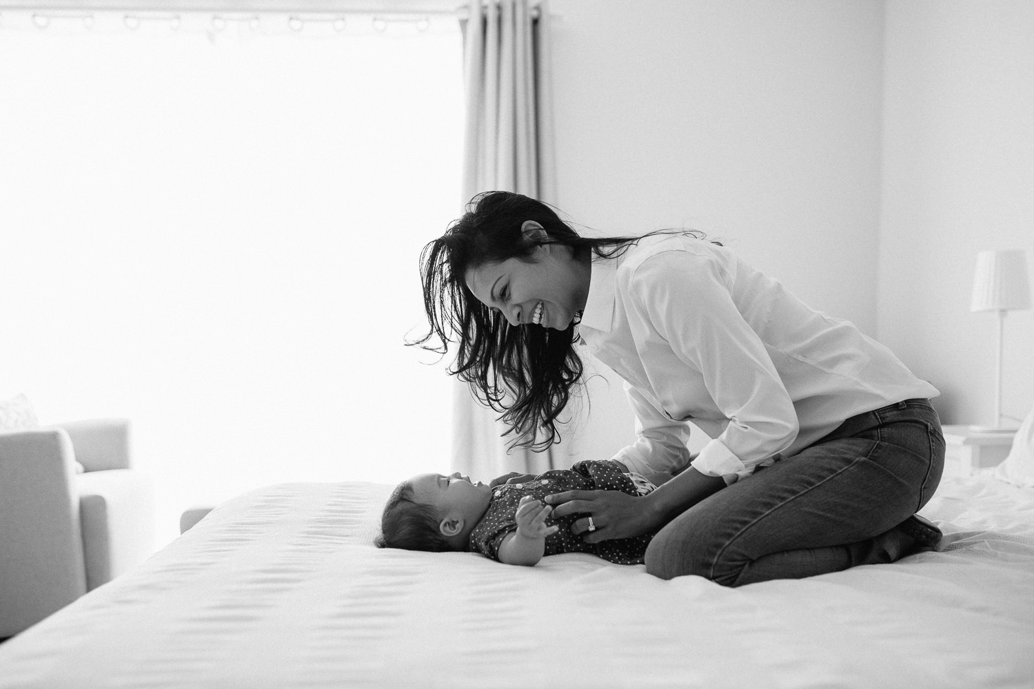 6 month old baby girl lying on bed, mom leaning over her smiling - Markham Lifestyle Photography