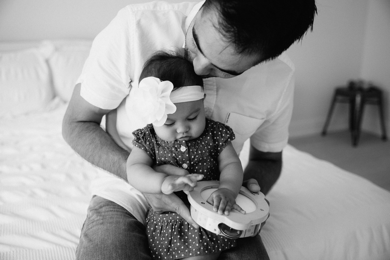 father sitting with 6 month old baby girl in his lap, kissing the top of her head - Markham In-Home Photography