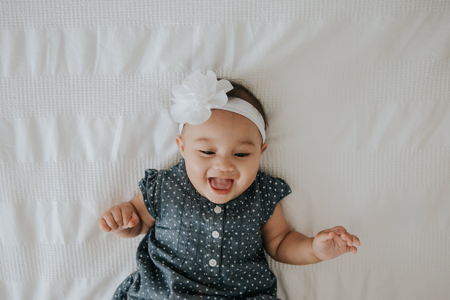 6 month old baby girl in blue and white polka dot dress lying on bed laughing - Markham In-Home Photos