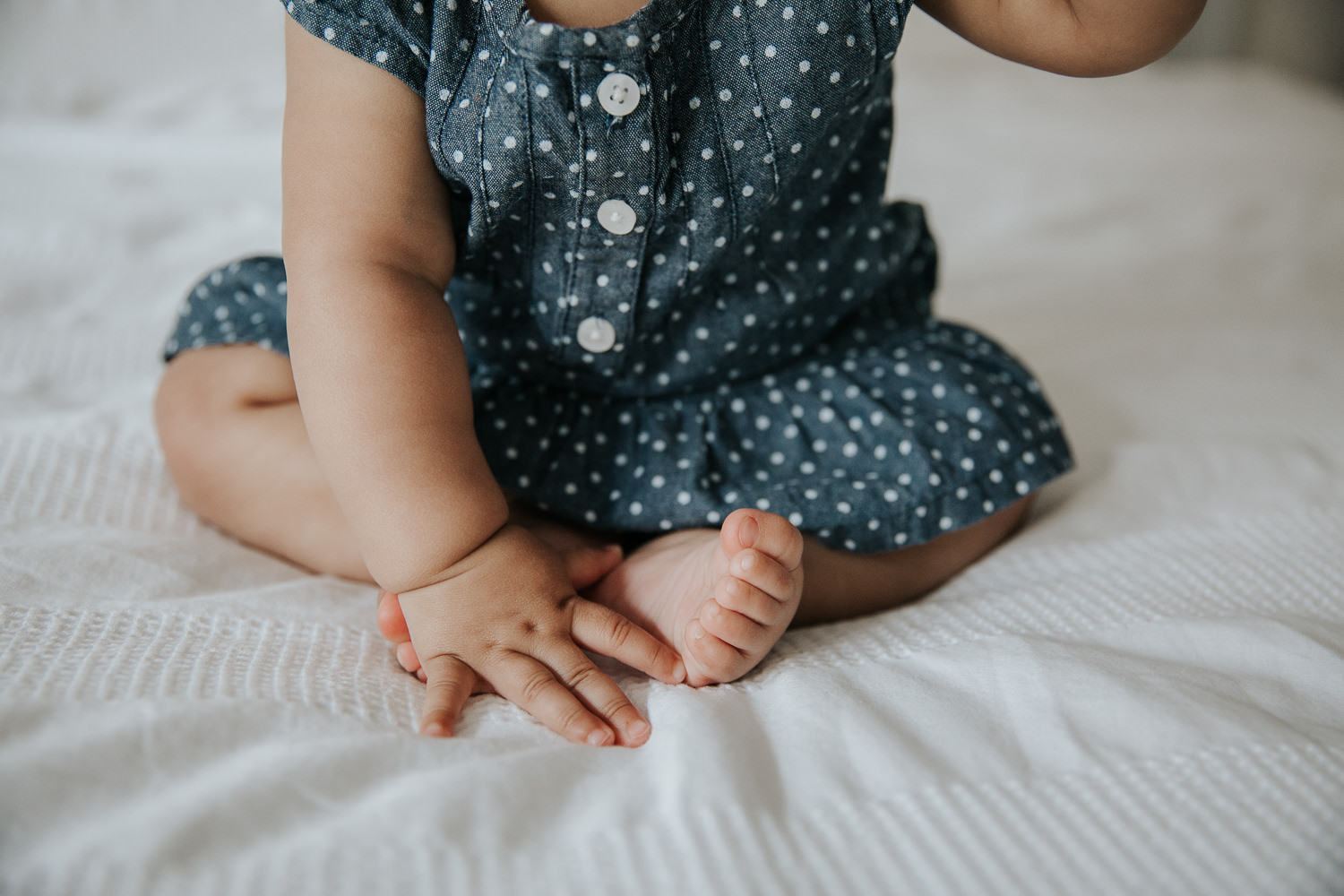 6 month old baby girl in blue and white polka dot dress sitting on bed, close up of hand and feet - Newmarket Lifestyle Photos