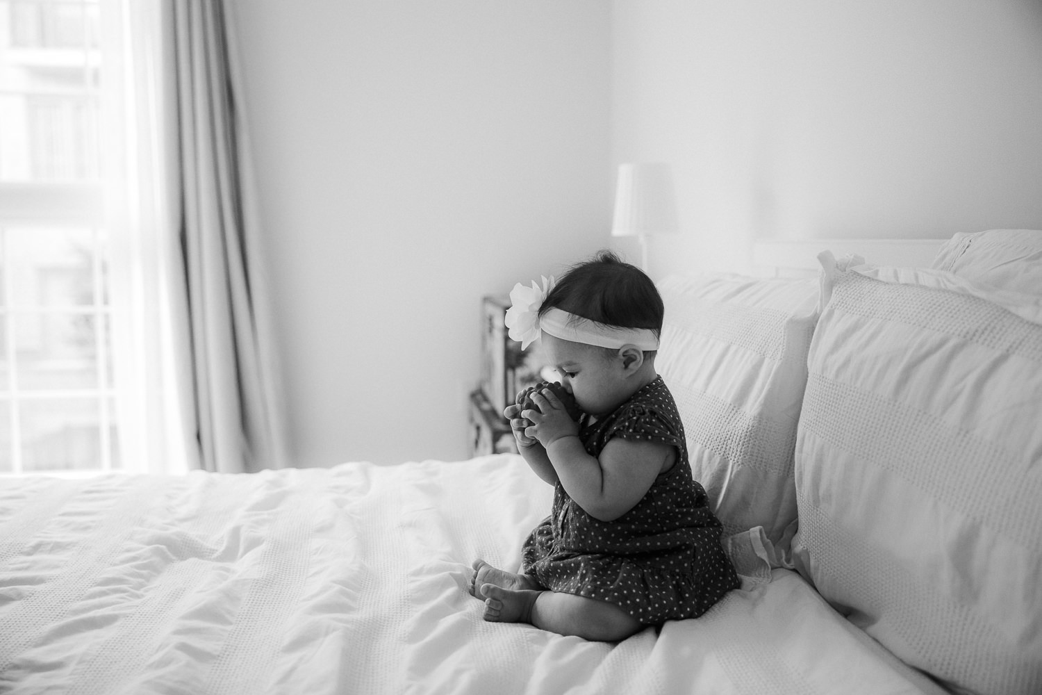 6 month old baby girl sitting on bed chewing on toy - Stouffville Lifestyle Photos