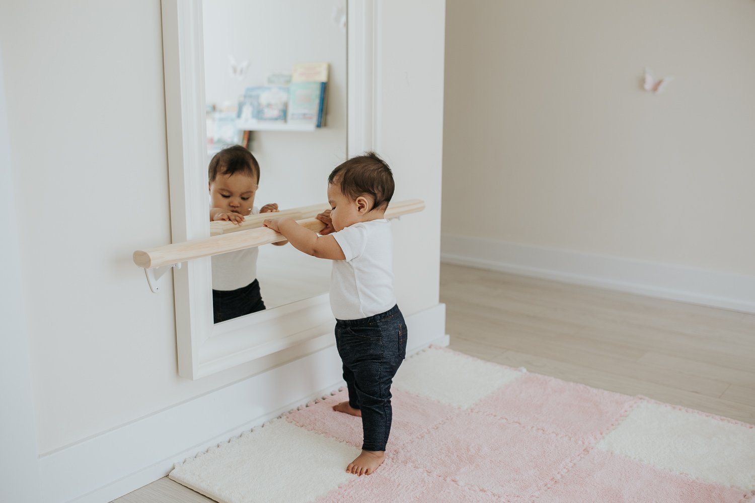 6 month old baby girl standing holding onto bar and looking in mirror - Barrie Lifestyle Photography